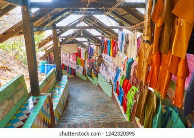 SAGAING, MYANMAR - FEBRUARY 21, 2018: Walk covered alleyway of U Min Thonze market with stalls, offering traditional cotton t-shirts, embroidered blouses, longyi skirts, on February 21 in Sagaing