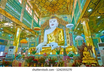 SAGAING, MYANMAR - FEBRUARY 21, 2018: The flowers on altar in Image House of Soon Oo Ponya Shin Paya (Summit Pagoda), the  Buddha statue is surrounded by fine mirrorwork, on February 21 in Sagaing