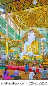 SAGAING, MYANMAR - FEBRUARY 21, 2018: The prayer hall of Soon Oo Ponya Shin Pagoda (Summit Pagoda) with giant Buddha Image in golden robe and shimmering glass tiles on walls, on February 21 in Sagaing