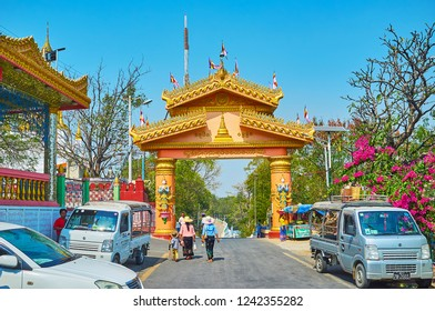 SAGAING, MYANMAR - FEBRUARY 21, 2018: The scenic gate of Soon Oo Ponya Shin Pagoda with shaped gilt ornaments and pyatthat decorative roof, on February 21 in Sagaing