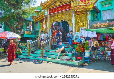 SAGAING, MYANMAR - FEBRUARY 21, 2018: The crowded entrance to Soon Oo Ponya Shin Pagoda (Summit Pagoda), people leave their footwear on the steps and go to the Shrine, on February 21 in Sagaing
