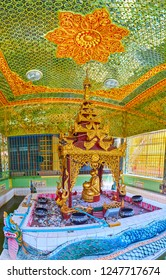 SAGAING, MYANMAR - FEBRUARY 21, 2018: Small shrine in Soon Oo Ponya Shin Paya with gilt statue of Nat (Spirit), sitting in carved pavilion and surrounded by donation boxes, on February 21 in Sagaing.