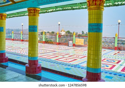 SAGAING, MYANMAR - FEBRUARY 21, 2018: The view on the open air terrace of Soon Oo Ponya Shin Paya (Summit Pagoda) from its covered hallway with scenic tiled columns, on February 21 in Sagaing