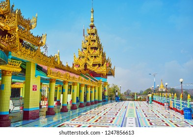 SAGAING, MYANMAR - FEBRUARY 21, 2018: The buildings of Soon Oo Ponya Shin Paya (Summit Pagoda) with golden pyatthat roofs, tiled columns and floor with geometric patterns, on February 21 in Sagaing