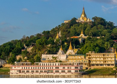 Sagaing, Myanmar - November 19:  A cruise ship stops in front of a temple hill in the old capital Sagaing at sunrise. November 19, 2015 in Sagaing, Myanmar