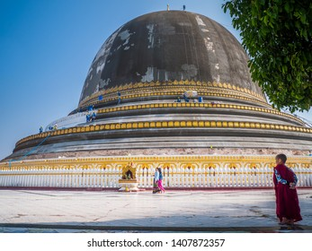 Sagaing, Myanmar-Feb12'19: Little monk stands in front of Kaunghmudaw Pagoda that is repaired by worker, this is a large pagoda on the northwestern outskirts of Sagaing in Myanmar has unique shape.
