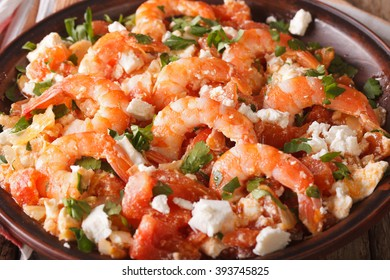 Saganaki prawns with feta cheese and tomatoes close-up on a plate. horizontal