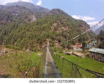 Sagarmatha National Park, Nepal - May 2019: Suspension bridge over the precipice with colorful flags in nepal