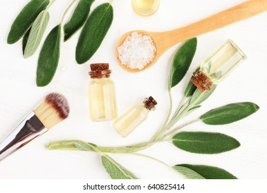 Sage essential oil (Salvia officinalis). Aroma bottles and fresh green medicinal plant leaves, top view. Botanical spa treatment