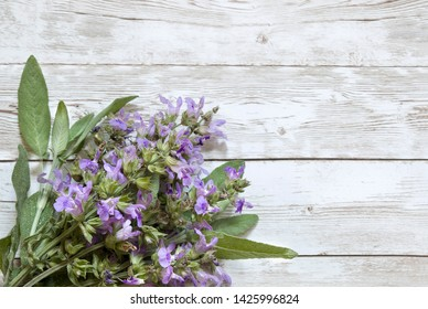 Sage leaves and flower (Salvia officinalis) on old wooden table.blooming Salvia officinalis.Top view