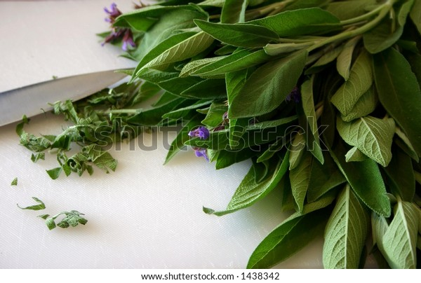 Sage leaves on white cutting mat with knife