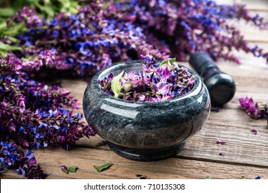 Sage plant and  mortar on old rustic wooden background. Alternative health care fresh salvia flowers.