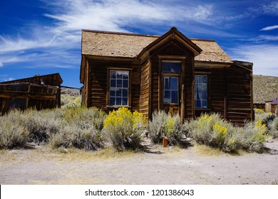 Sagebrush surrounds a long abandoned house in desert ghost town Bodie, California, a historic Old West mining center whose heyday was 1877 to 1881.