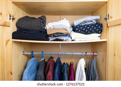 Sagging shelf with lots of clothes in a wood  wardrobe. Concept of abundance of personal things and  consumerism.