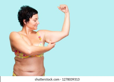 Saggy or loose skin on the hands. girl shows the flaws of her figure. Fat Woman Body. blue background. isolated. Close-up. - Image.