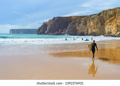 SAGRES, PORTUGAL - OCTOBER 30, 2018: Young man walking by sandy beach with surfboard. ALgarve is a famous surfing destination in Portugal