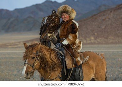 SAGSAY, MONGOLIA - SEP 28, 2017: Kazakh woman Eagle Hunter traditional clothing, while hunting to the hare holding a golden eagle on his arm in desert mountain of Western Mongolia.
