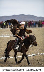 SAGSAY, MONGOLIA - SEP 30, 2017: Berkutchi - Kazakh hunter with Golden eagle, while hunting to the hare in desert mountain of Western Mongolia.