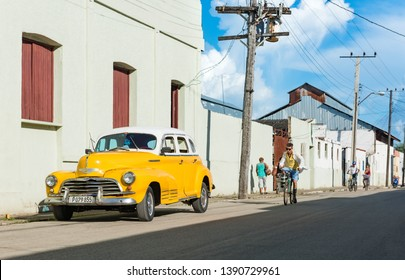 Sagua la Grande, Cuba - September 21, 2018: American yellow 1946 Chevrolet Fleetmaster vintage car with white roof parked on the side street in Sagua la Grande Cuba - Serie Cuba Reportage