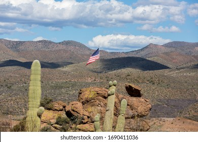 Saguaro cactus with desert background cactus and rocks with American flag flying