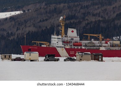 Saguenay, Québec/Canada - 03 19 2019 : An ice breaker ship from the Canadian coast guard in action with ice fishing village.