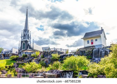 Saguenay, Canada - June 3, 2017: Chicoutimi park in Quebec with river and water flowing in summer and view of church