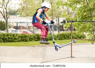 Saguenay, Canada - June 3, 2017: Downtown city summer park in Quebec with young teenager boy skating, performing tailwhip tricks, stunts on scooter on metal rusty playground ramp, skatepark