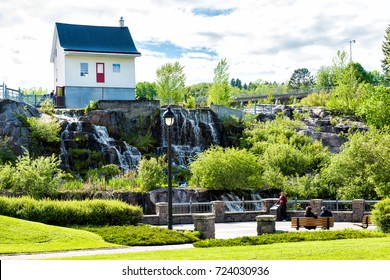 Saguenay, Canada - June 3, 2017: Chicoutimi park in Quebec with river and water flowing in summer and people
