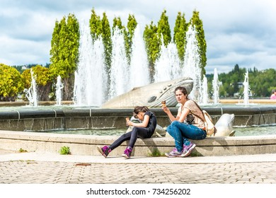 Saguenay, Canada - June 3, 2017: People, mother and daughter, sitting by whale fountain in downtown city park in Quebec eating, licking ice cream during hot summer day
