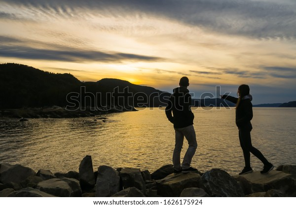 Saguenay, Canada - september 2019: Young couple standing on rocks and watching the sunset in Petit-Saguenay