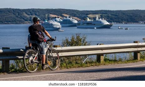 Saguenay, Quebec/Canada - 09 16 2018 : Cruises boats docked at the port of Saguenay, cyclist looking at boats.