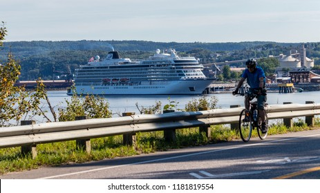 Saguenay, Quebec/Canada - 09 16 2018 : Cruises boats docked at the port of Saguenay, cyclist passing by.