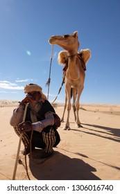 Sahara, Atar region, Mauritania - 13 January 2019: Berber nomad with hic camel in Sahara desert.