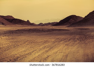 Sahara desert - mountain landscape with dusty offroad and stone hills on a horizon. Exotic adventure or expedition in arid wilderness, extreme travel to Egypt. The Martian landscape in Africa.