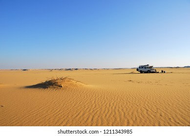 Sahara Desert safari off-road vehicle parking for camp into the sand desert nearby Dakhla oasis in Egypt, Africa