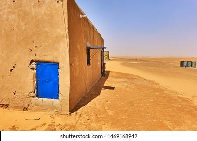 Sahara desert, Sudan, February 10., 2019: Clay hut with a blue door in the desert