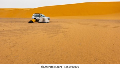 Sahara desert, Sudan, February 7, 2019: Camping in the Sudanese desert with two small tents, an off-road vehicle and a sand dune in the background