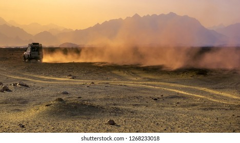 Sahara desert at sunset - mountain landscape with a dusty road and driving the off-road car. Traveling by car - idea for active adventure in wildlife, scientific expedition or extreme travel on a SUV.