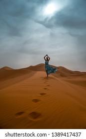 29c95513582 Sahara / Morocco - February 14 2019: Women in blue and white dress walking  on