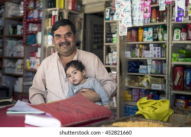 SAHARAN, INDIA - Jun 05, 2016: Businessman look in front smiling, hold his infant, sit at grocery shop.