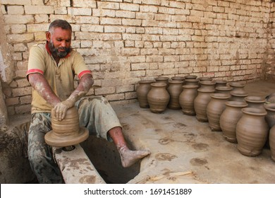 Sahiwal, Punjab, Pakistan - March 28, 2017: Pottery art A man making mud vase by hand in the village shop.