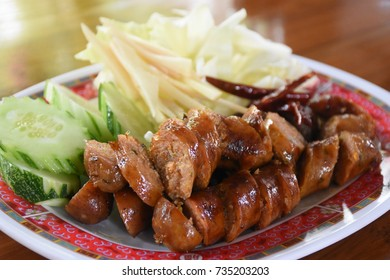 SAI AUA (NOTRHERN THAI SPICY SAUSAGE) is a type of smoked roast with sticky rice. Garnish with fresh ginger, fresh chilies, shallots, and lemons.