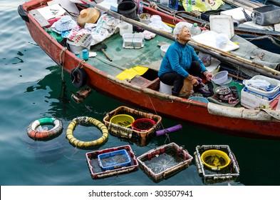 SAI KUNG, HONG KONG - APRIL 16, 2015 : An unidentified old woman sells seafood in her boat on April 16, 2015 at Sai kung fisherman village, Hong Kong.