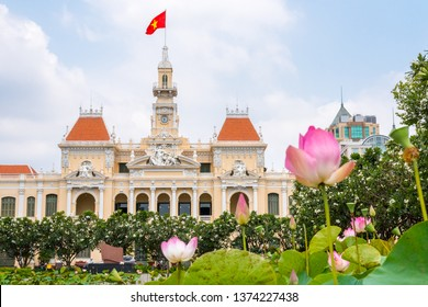 Saigon City Hall (or Ho Chi Minh City People's Committee) with pink lotus flowers and blooming plumeria trees in the foreground (blurred). One of the top tourist attractions of the city. Vietnam.