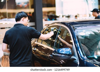 SAIGON EXHIBITION AND CONVENTION CENTER (SECC), HO CHI MINH CITY, VIETNAM - OCTOBER 2018: Unidentified man car cleaner. A man cleaning car with microfiber cloth, car detailing (or valeting) concept