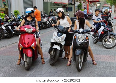 SAIGON - FEB 4, 2015 - Young women on motorbikes face heavy traffic in downtown Saigon (Ho Chi Minh City),  Vietnam