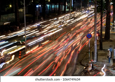 SAIGON, VIETNAM, DEC 14 2017, Dense traffic at night intersection with blurred lights passing through motorbikes and vehicles.