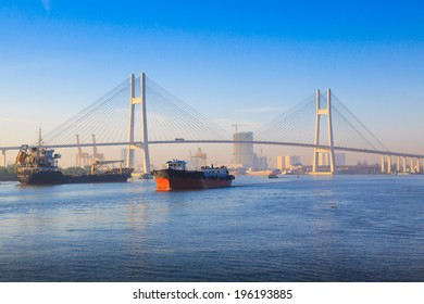 SAIGON, VIETNAM - DEC 16: The cargo ships in Saigon river going through Phu My bridge, Vietnam.  On Dec 16, 2012.