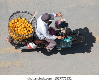 SAIGON, VIETNAM, DEC 17 2017, Motorcyclist rides with basket full of orange, Saigon. Delivery of fresh fruits in the streets of Ho Chi Minh city.