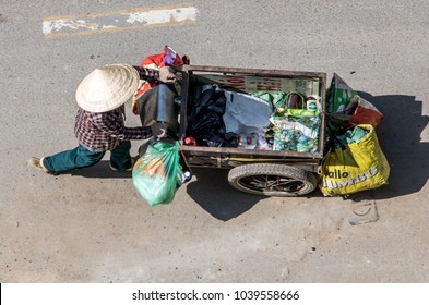 SAIGON, VIETNAM, DEC 17 2017, Collection of recyclable waste in the streets of Ho Chi Minh city. Vietnamese woman pushing a cart full of bags, Saigon city.